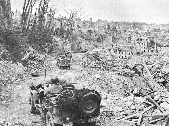 Jeep 219. dělostřeleckého praporu 35. pěší divize projíždí ruinami St. Lö