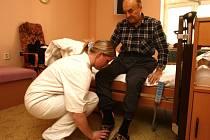 """Fyzioterapeutka Lucie Hergetová pomáhá jednomu z klientů plzeňského hospicu Jiřímu Simandlovi. Ten si přístup zaměstnanců pochvaloval. Jedinou jeho připomínkou bylo umístění domu přímo v centru města. """"Chybí mi tady park, zeleň,"""" říká"""