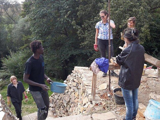 Dobrovolníci v Pivovaru Chříč pracují na zdi. Je to dřina, ale pracují rádi a ještě se přitom něco přiučí