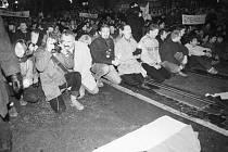 Dav lidí na Národní třídě byl obklíčený neprodyšně z obou stran, lidé si sedají s rukama nad hlavou a volají: Máme holé ruce! Nechceme násilí! či Jakeše do koše!