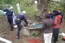 pokrývají poklop obecní studny v Tisu u Blatna. Hasiči vodu vypustili. Chemikálie tu rozlily nejspíš děti