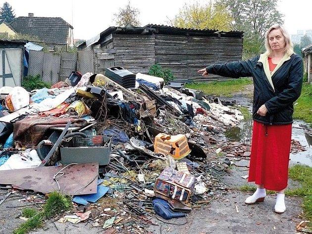 Magdalena Rožičová ukazuje na nepořádek před domem. Na hromadě najdete kusy elektroniky, aut i ošacení