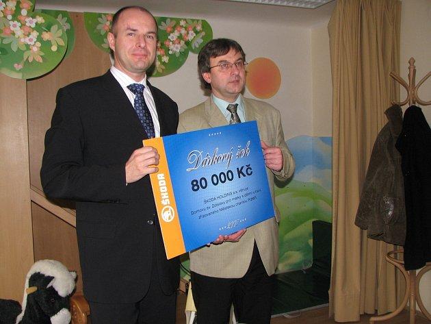 Personální ředitel Škody Holding Josef Bernard předává řediteli Městské charity v Plzni Pavlu Janouškovcovi šek na 80 tisíc.