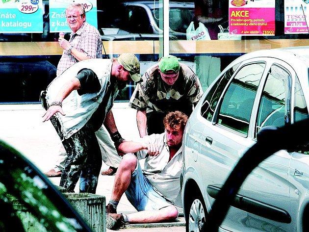 """Kamarádi se snaží """"odklidit"""" opilého a právě se probudivšího muže na klidnější místo ve stínu. Podobné výjevy mohou návštěvníci """"malého"""" Teska vidět téměř každý den. Ještě horší je, když opilci žádají kolemjdoucí o peníze nebo jsou agresivní."""