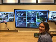 Na snímku je městská policistka před obrazovkami ukazujícími pohyb v ulicích snímaný kamerami.