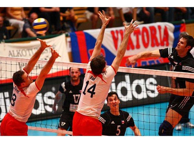 TVRDÁ RÁNA. Český volejbalový reprezentant Michal Rak (vpravo) smečuje přes slovenský blok během včerejšího kvalifikačního utkání o postup na mistrovství Evropy 2009.