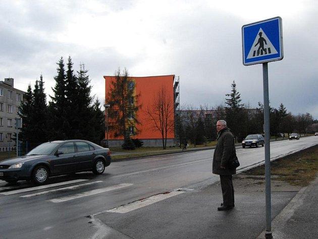 Muž čeká na přechodu v Třemošné, až některé z aut zastaví.