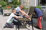 Kluci z MŠ zkouší pilovat se seniorským dobrovolníkem z TOTEMu.