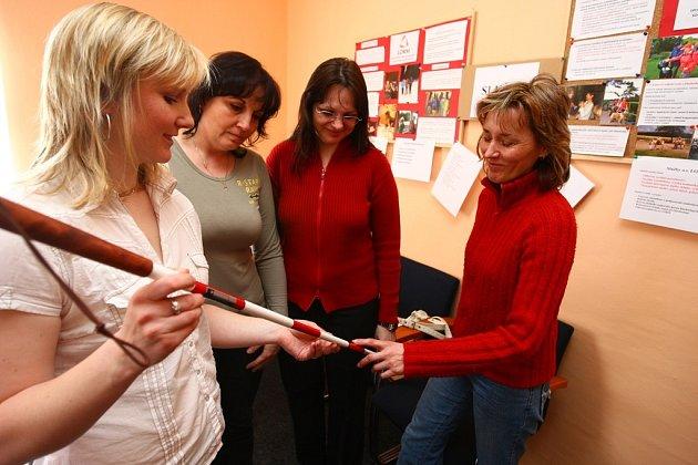 Věra Dirlbecková ukazuje pomůcku hluchoslepých - červenobílou hůl, která  upozorňuje veřejnost na toto postižení.