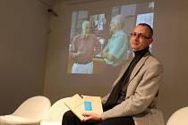 Petr Domanický ze ZČG s anglickým i českým vydáním knihy vzpomínek Willa Semlera Rodinné těžítko. Autor knihy, v Austrálii žijící letos třiadevadesátiletý Will  Semler, je zachycen v pozadí zcela vlevo na fotografické projekci