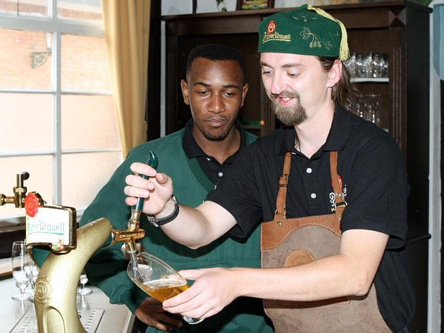 Český výčepní Václav Vanya z Kadaně předvádí, jak se čepuje pivo. Jeho počínání přihlíží Jihoafričan Moses Ndhlovu