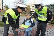Policisté rozdávali reflexní samolepky. Mnohé děti si je hned lepily na školní brašny