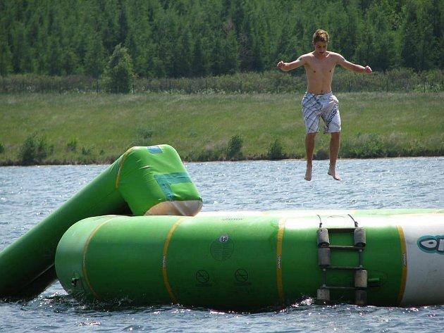 Jeden z prvních návštěvníků sokolovské vodní nádrže Michal zkoušel v pátek své umění na trampolíně. Na tu však musel nejdříve doplavat, protože je umístěna na vodní ploše