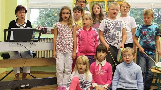 Malí zpěváci z dětského souboru Lukaváček nacvičují písně za doprovodu vedoucí Nadi Květoňové (úplně vlevo)