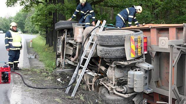 Z havarovaného kamionu naloženého sutí vytékal hydraulický olej. Ten hasiči v pondělí dopoledne odčerpali a kamion pomocí dvou autojeřábů postavili na kola