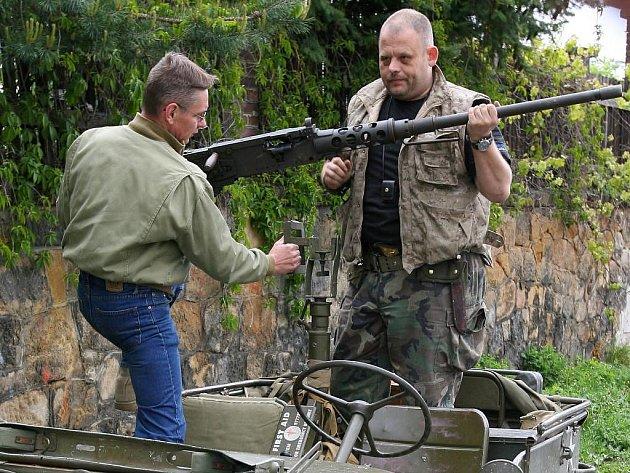 Michal Kindl (vpravo) a Ondřej Čechura nakládají těžký americký kulomet M2 Browning na džíp