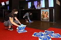 Martina Pitnerová s kolegyněmi z multikina CineStar připravuje vstupní prostory kina u pokladen na přivítání prvních diváků.