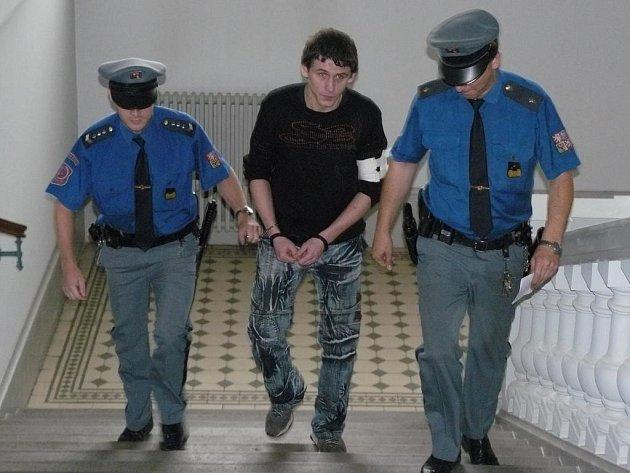 Justiční stráž přivádí k soudu Antonína Kotrče
