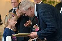 Šestiletá Nikolka Kodalíková přebírá ocenění z rukou prezidenta Miloše Zemana