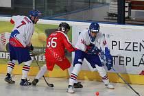 Čeští hokejbalisté Michal Dědič a Pavel Kubeš bojují v prvním utkání mistrovství světa v Plzni se švýcarským útočníkem Martinem Reberem.