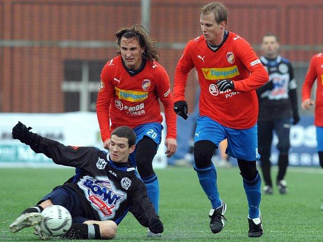Kladenský David Bartek (na zemi) se snaží zpracovat míč před dvojicí dobíhajících plzeňských fotbalistů Davidem Limberským (vpravo) a Petrem Jiráčkem