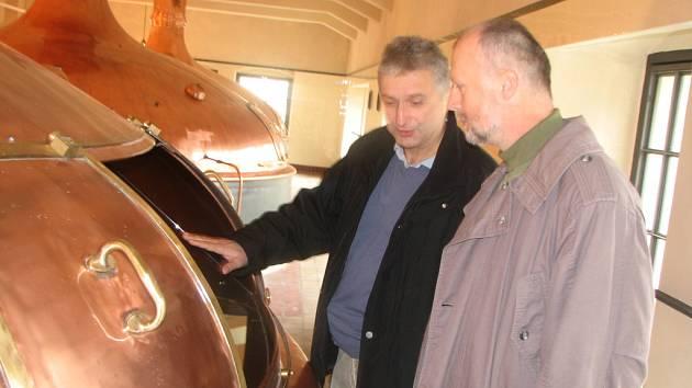 Šéf technických služeb plzeňského pivovaru Vladimír Burian debatuje nad jednou ze rmutovacích kádí na staré varně s restaurátorem kovových částí varny Tomášem Flimelem.