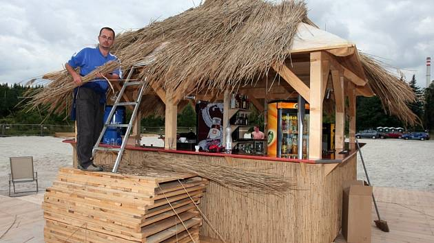 V pátek ve dvanáct otvíráme, zněl vzkaz Romana Bakaly (na snímku) zástupce investora, který v Plzni Doubravce vybudoval písečnou pláž u řeky. V určený čas jsme Bakalu zastihli na střeše baru, který uprostřed pláže stojí, jak tam umisťuje rákosové snopy