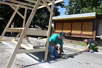 Pracovníci už ve čtvrtek začali stavět dřevěné stánky, na nichž budou obchodníci nabízet své zboží sedmadvacátého června na bleších trzích.