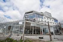 Dodnes nedokončená budova začala vznikat v 90. letech minulého století. Stavební povolení získalo tehdy jen spodní patro, ne ale horní tři patra. Stavba je tak legální jen z části.