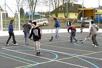 Děti si otevření hřišť užily. Na snímku zrovna hrají florbal na asfaltovém hřišti