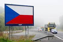 Billboardy překryté státní vlajkou vídají řidiči například na výpadovce z Plzně do Klatov.