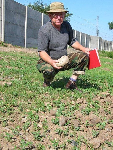 Jan Blaho ukazuje kameny, které mu na pozemek spolu s nekvalitní hlínou navezla nákladní auta. Mělo to být uvedení plochy do původního stavu, s tím ale on nesouhlasí