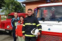 Před hasičskou zbrojnicí SDH Obora a jejich vozovým parkem se nechali vyfotit (zleva) Tomáš Svoboda, Radka Svobodová a Jonáš Volek