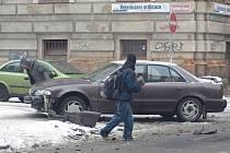 V plzeňské ulici Kardinála Berana to klouzalo řidičům i chodcům. Na snímku je vůz, který tu havaroval v úterý ráno. Kolemjdoucí v pozadí jen s obtížemi balancuje na kluzké silnici
