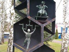 Monument s ukradenou bronzovou sochou muže zvedajícího hřídel.
