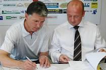 Trenér Jaroslav Šilhavý podepisuje na sobotní tiskové konferenci smlouvu s Viktorií Plzeň, vpravo přihlíží sportovní manažer Viktorie Adolf Šádek.