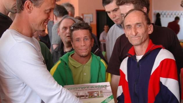 Fotbalový trenér  Stanislav Purkart předává knihu Vzestupy a pády Viktorie Plzeň  uživatelům služeb Domova pro osoby se zdravotním postižením ve Stodě
