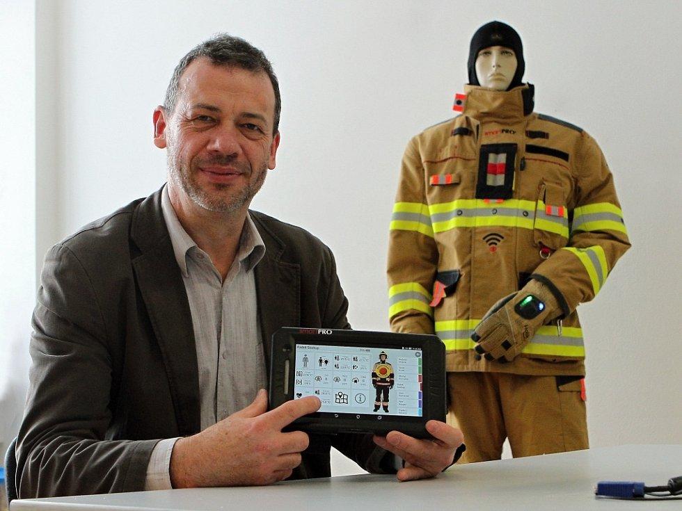 Na chytrém zásahovém obleku pracovali vědci z RICE šest let. Na fotografii je vedoucí výzkumného týmu Aleš Hamáček, který ukazuje elektronickou řídicí jednotku obsahující mikropočítač s operačním systémem.