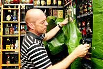 Obchodníci prodávající alkohol přivítali zmírnění prohibice. Bohumil Hůrka z prodejny F. L. Věk sundavá z regálu plachtu.