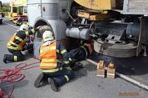 Motorkář při nehodě skočnil pod předním kolem nákladního auta. Vyprostit ho museli hasiči