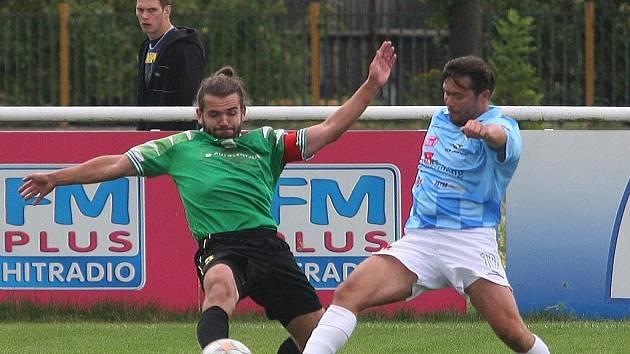 Domažlický fotbalista zastavuje akci útočníka Chrástu Václava Bezdičky ve včerejším pohárovém duelu, který skončil výhrou Chodů 2:1.
