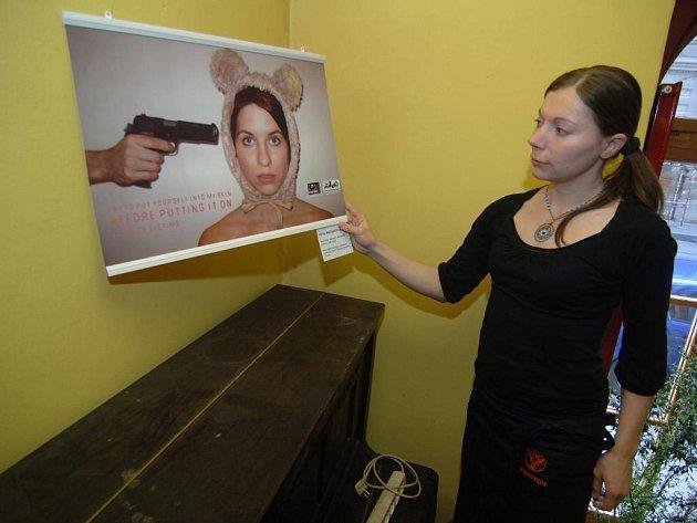 Tereza Karbanová z Inkognita ukazuje plakát zaměřený proti kožešinové módě Věry Maštalířové. Ten je společně s dalšími patnácti díly vystaven v kavárně