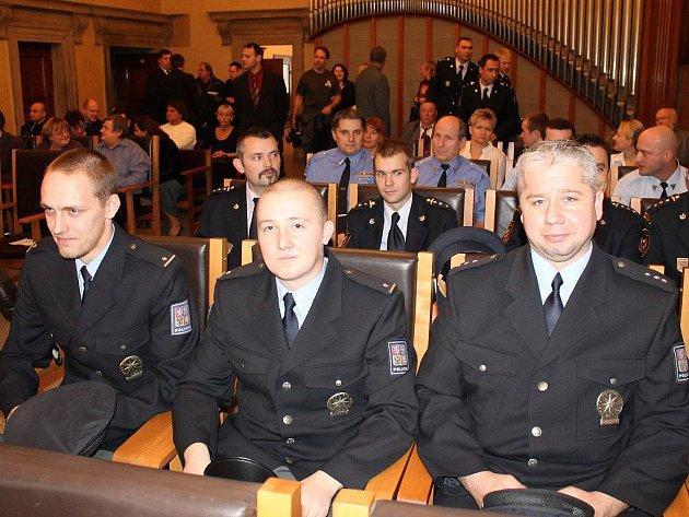 Policisté (zprava) Petr Soukup, Tomáš Bombička a Milan Krch před oceněním na radnici. Za nimi v řadě hasiči, kteří zasahovali u nehody a detonací tlakových bomb u tunelu Valík