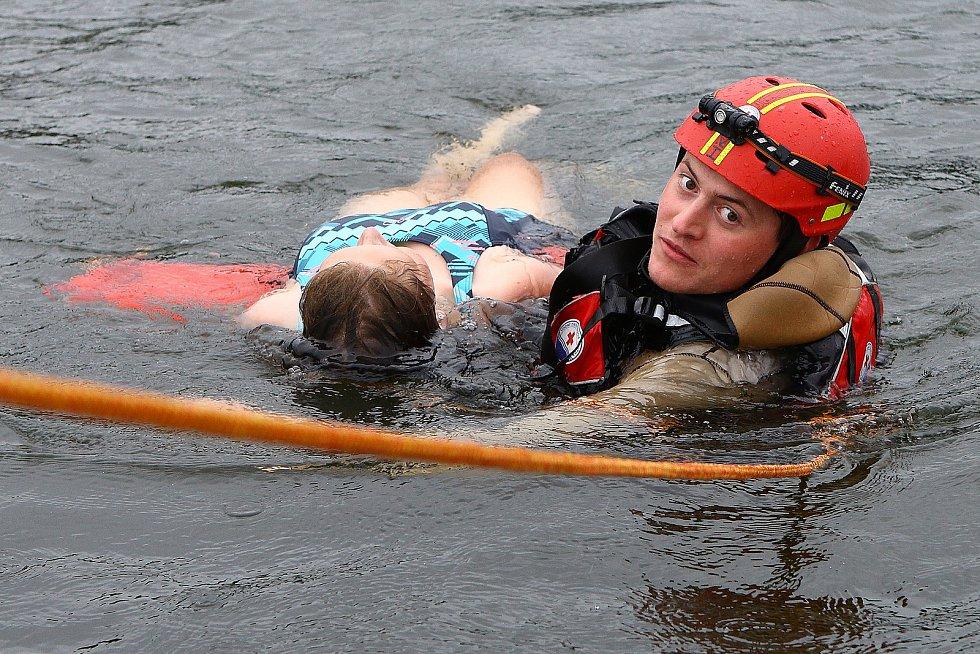 16 - Záchranáře zasahujícího ve vodě k lodi přitahují kolegové z paluby záchranářského prámu pomocí lana, které jej zároveň jistí.
