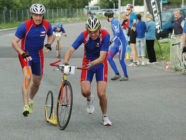 Ladislav Provod (vpravo) přebírá koloběžku od svého reprezentačního kolegy Richarda Jisla při závodě štafet na mistrovství Evropy v koloběhu na okruhu v Plzni na Lopatárně.