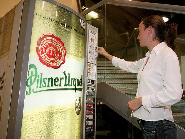 Host návštěvnického centra pivovaru si nechává lustrovat občanský průkaz, aby mohla dostat z prvního pivomatu v Plzni plechovku piva.