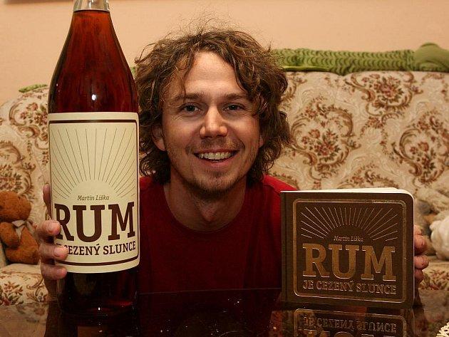 Plzeňský herec a režisér Vilém Dubnička ukazuje knihu Rum cezený sluncem a rum se speciální etiketou, kterým byla sbírka pokřtěna