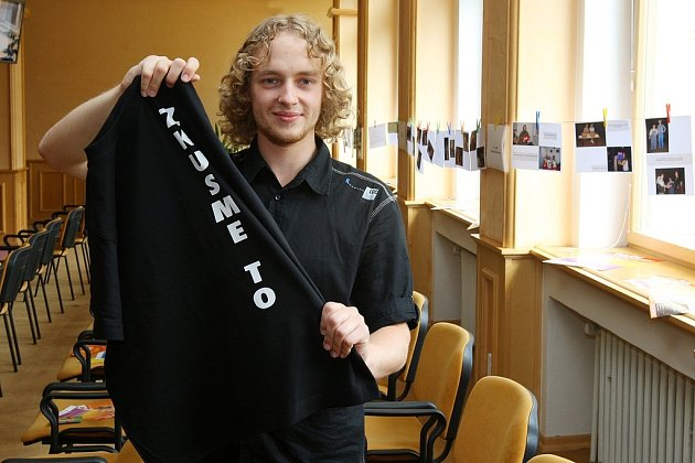 Asistent Aleš Mentberger ukazuje triko  programu Zkusme to sociálně aktivizační služby.