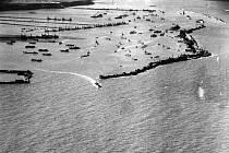 Na snímku umělý přístav Mulberry B, který spojenci sestavili u Arromanches poblíž pláže Gold v britském sektoru. Přes tento přístav někdy nazývaný Port Winston prošlo dva a půl milionu lidí, půl milionu vozidel a čtyři miliony tun dodávek