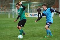 Rokycanský Karel Vileta (s míčem) v souboji s hráčem Holýšova. Snímek je z podzimního utkání krajského přeboru (3:0).